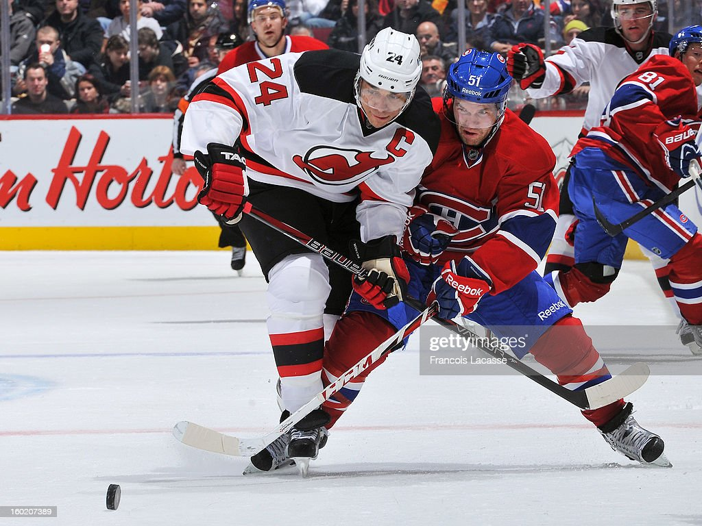 David Desharnais #51 of the Montreal Canadiens battles for a loose puck with captain Bryce Salvador #24 of the New Jersey Devils during the NHL game on January 27, 2013 at the Bell Centre in Montreal, Quebec, Canada.