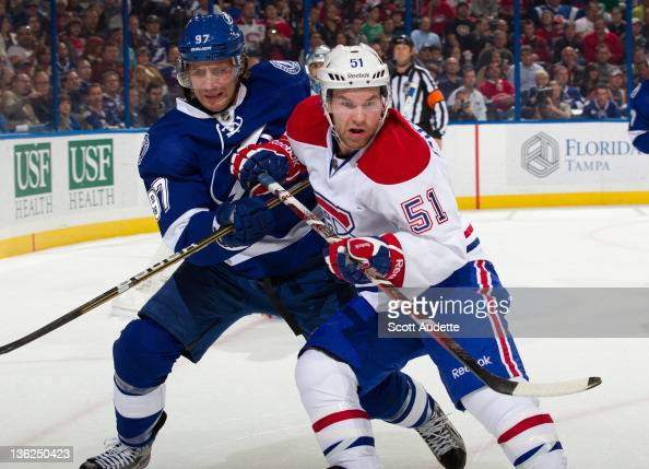 David Desharnais of the Montreal Canadiens battles for position against Matt Gilroy of the Tampa Bay Lightning at the St Pete Times Forum on December...