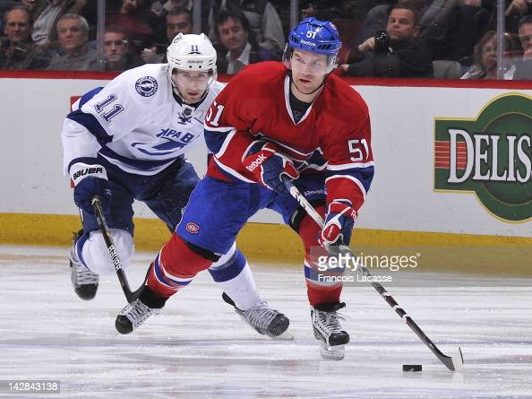 David Desharnais of the Montreal Canadiens carries the puck as Tom Pyatt of the Tampa Bay Lightning pressures from behind during the NHL game on...