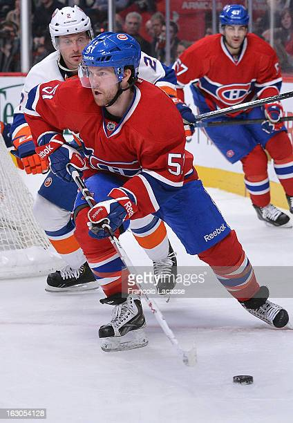 David Desharnais of the Montreal Canadiens controls the puck and skates wide as Mark Streit of the New York Islanders pressure during an NHL game on...