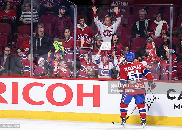 David Desharnais of the Montreal Canadiens gives a puck to a fan during the warmup period before the game against the Columbus Blue Jackets in the...