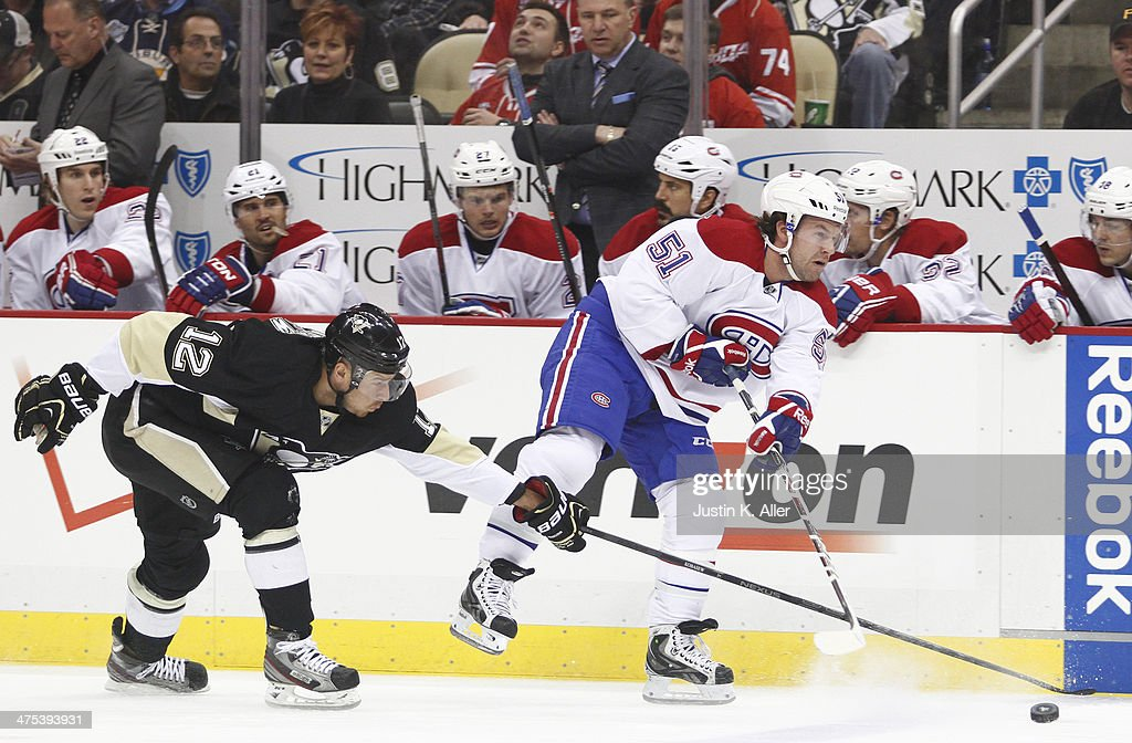 David Desharnais of the Montreal Canadiens handles the puck in front of Chuck Kobasew of the Pittsburgh Penguins during the game at Consol Energy...