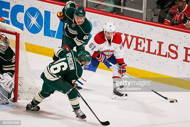 David Desharnais of the Montreal Canadiens handles the puck with Jared Spurgeon and Mikael Granlund of the Minnesota Wild defending during the game...