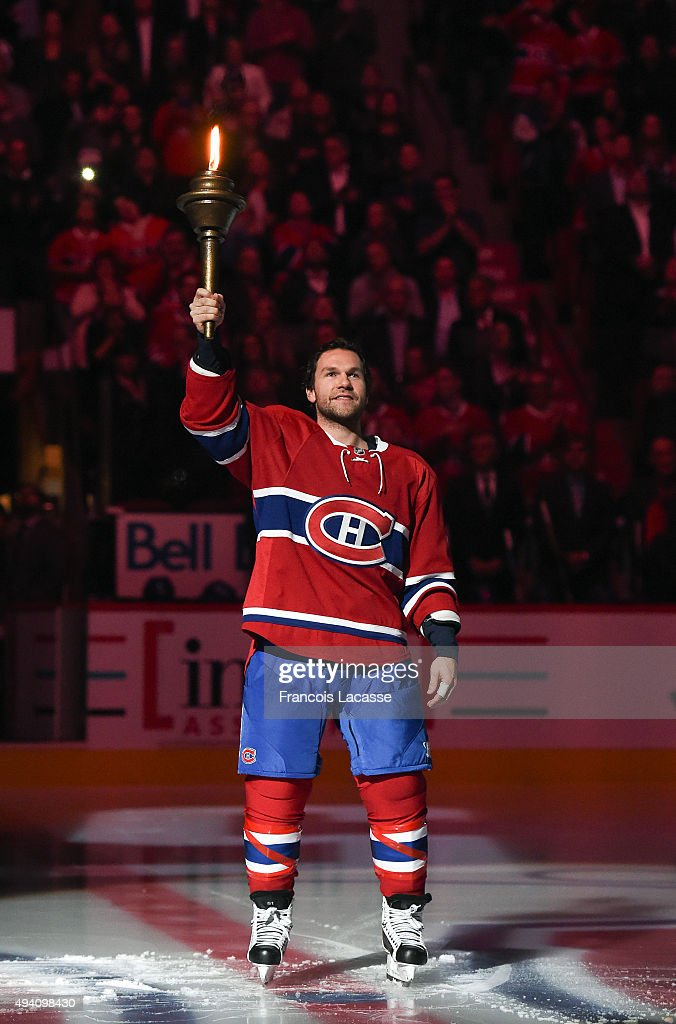 David Desharnais of the Montreal Canadiens holds the flame during the pre game ceremony prior to the NHL game against the New York Rangers at the...