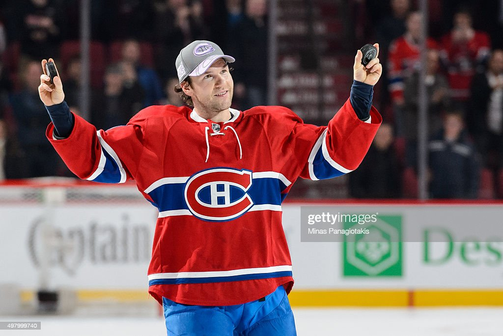 David Desharnais of the Montreal Canadiens holds up two pucks after being awarded the first star of the match during the NHL game against the...
