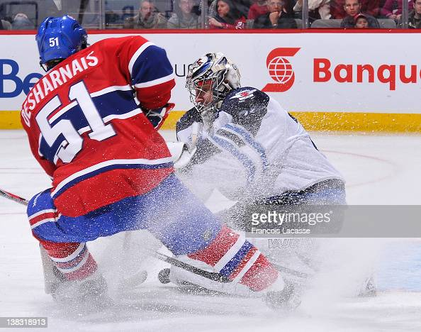 David Desharnais of the Montreal Canadiens is being stopped by goaltender Ondrej Pavelec of the Winnipeg Jets during the NHL game on February 5 2012...