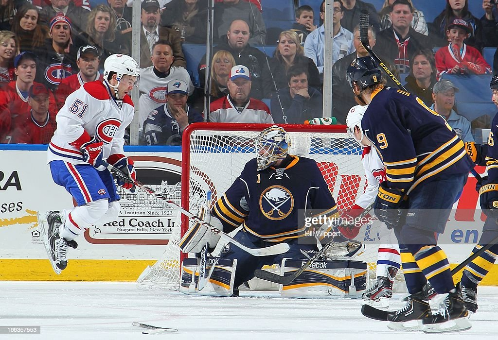 David Desharnais #51 of the Montreal Canadiens jumps to screen goaltender Jhonas Enroth #1 of the Buffalo Sabres on a third-period goal by P.K. Subban (not shown) on April 11, 2013 at the First Niagara Center in Buffalo, New York. Montreal defeated Buffalo, 5-1.
