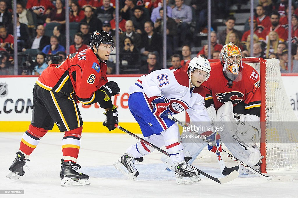 David Desharnais #51 of the Montreal Canadiens looks for an opportunity in front of the net as Joey MacDonald #35 and Dennis Wideman #6 of the Calgary Flames defend during an NHL game at Scotiabank Saddledome on October 9, 2013 in Calgary, Alberta, Canada.