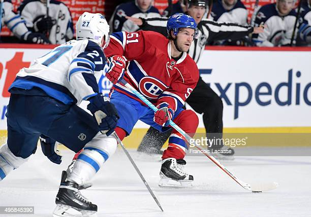 David Desharnais of the Montreal Canadiens looks to pass the puck against Nikolaj Ehlers of the Winnipeg Jets in the NHL game at the Bell Centre on...