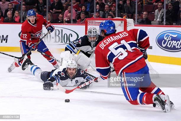 David Desharnais of the Montreal Canadiens stick handles the puck in front of Mark Stuart and Ondrej Pavelec of the Winnipeg Jets during the NHL game...