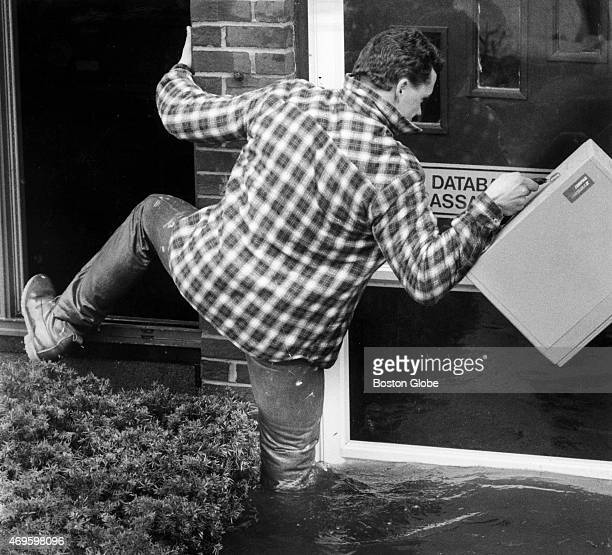 David Desnoyers who owns a publishing company on the edge of the Merrimack River steps out of his office window with computer equipment into kneedeep...