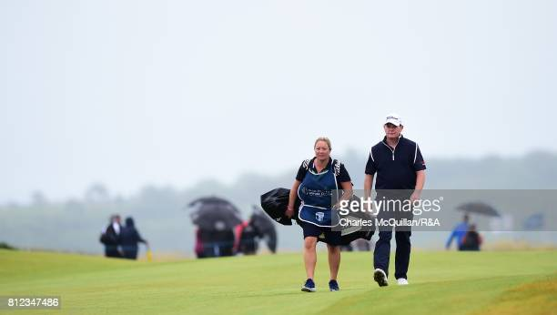 David Drysdale of Scotland makes his along the 18th fairway with his wife and caddy Vicky Drysdale during the final round at the Dubai Duty Free...