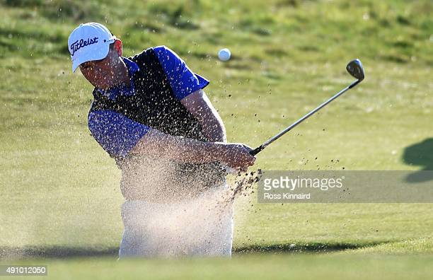 David Drysdale of Scotland plays out from bunker on the 18th green during the second round of the 2015 Alfred Dunhill Links Championship at the...