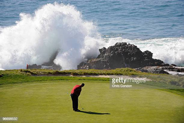 David Duval putts for birdie on as a wave crashes over the rocks during the final round of the ATT Pebble Beach National ProAm at Pebble Beach Golf...
