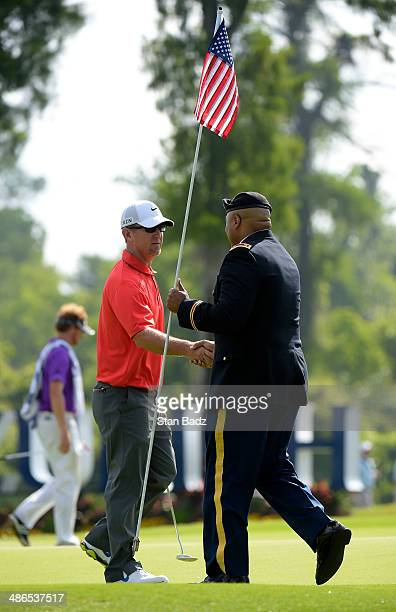 David Duval shakes hands with a US Army soldier attending the pin flag on the 17th green during the first round of the Zurich Classic of New Orleans...