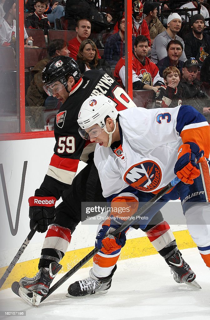 David Dziurzynski #59 of the Ottawa Senators battles in the corner against Travis Hamonic #3 of the New York Islanders, during an NHL game at Scotiabank Place on February 19, 2013 in Ottawa, Ontario, Canada.