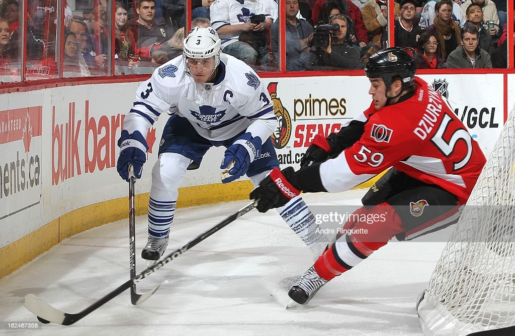 David Dziurzynski #59 of the Ottawa Senators controls the puck behind the net against Dion Phaneuf #3 of the Toronto Maple Leafs on February 23, 2013 at Scotiabank Place in Ottawa, Ontario, Canada.
