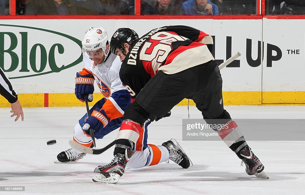 David Dziurzynski #59 of the Ottawa Senators faces off against <a gi-track='captionPersonalityLinkClicked' href=/galleries/search?phrase=Frans+Nielsen&family=editorial&specificpeople=634894 ng-click='$event.stopPropagation()'>Frans Nielsen</a> #51 of the New York Islanders on February 19, 2013 at Scotiabank Place in Ottawa, Ontario, Canada.