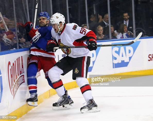 David Dziurzynski of the Ottawa Senators hits Dan Boyle of the New York Rangers into the boards during the third period at Madison Square Garden on...