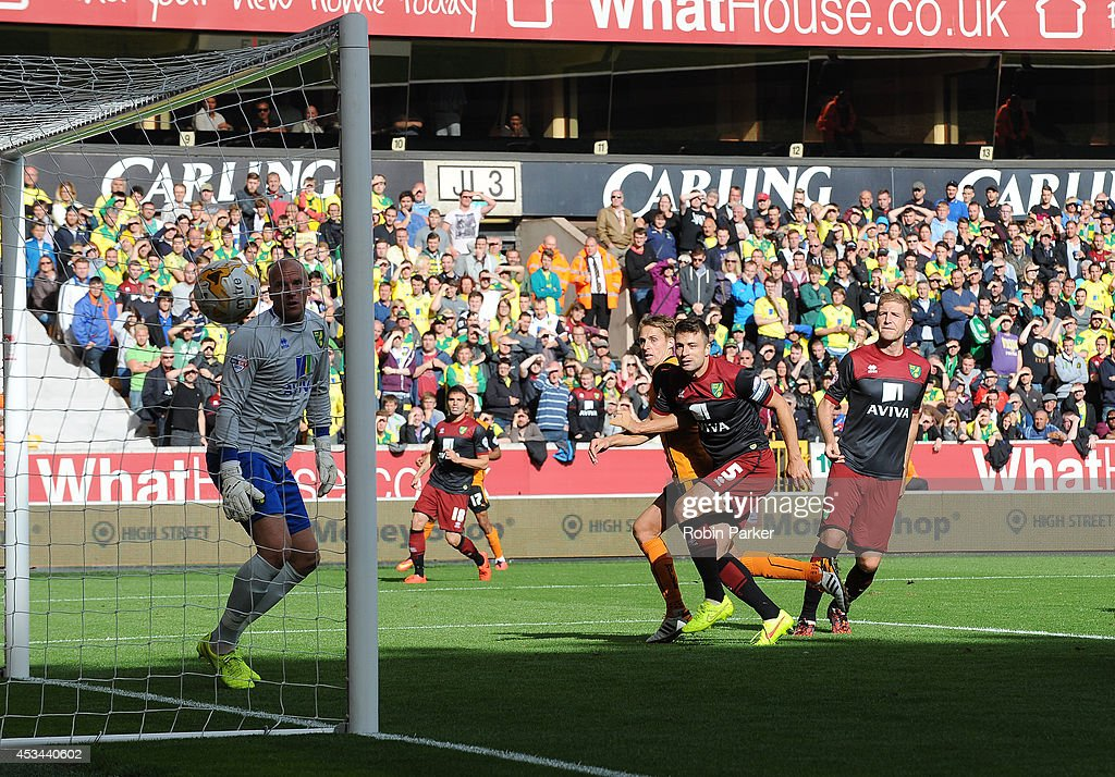 David Edwards of Wolverhampton Wanderers scores the opening goal of the game as he's challenged by <a gi-track='captionPersonalityLinkClicked' href=/galleries/search?phrase=Russell+Martin+-+Soccer+Player&family=editorial&specificpeople=13764026 ng-click='$event.stopPropagation()'>Russell Martin</a> of Norwich City during the Sky Bet Championship match between Wolverhampton Wanderers and Norwich City at the Molineux Stadium on August 10, 2014 in Wolverhampton, England.