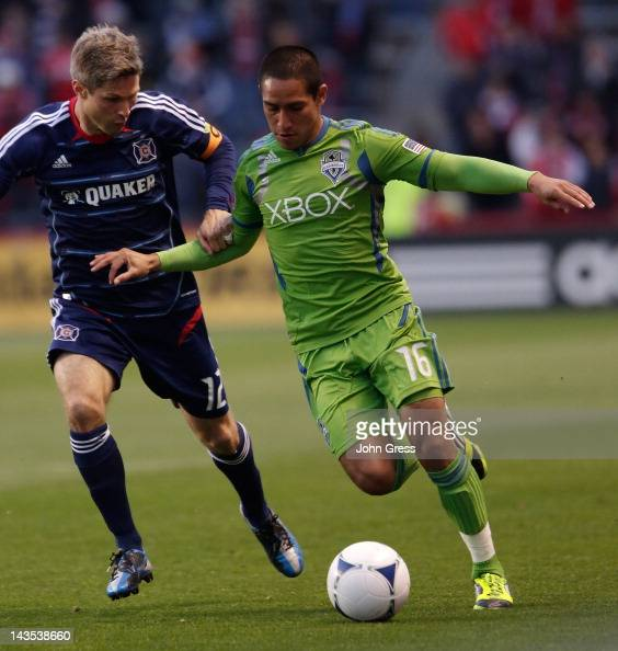 David Estrada of the Seattle Sounders FC struggles with Logan Pause of the Chicago Fire in the first half during their MLS match at Toyota Park on...