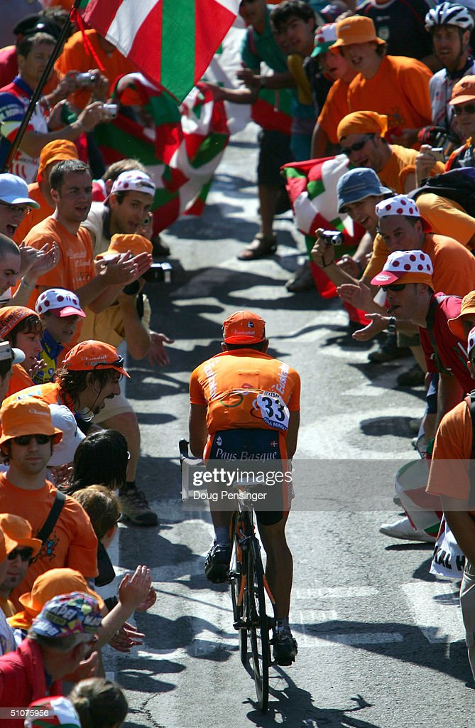 David Etxebarria of Spain and riding for EuskaltelEuskadi enters the 'orange tide' of Basque supporters during the final two kilometers of the...
