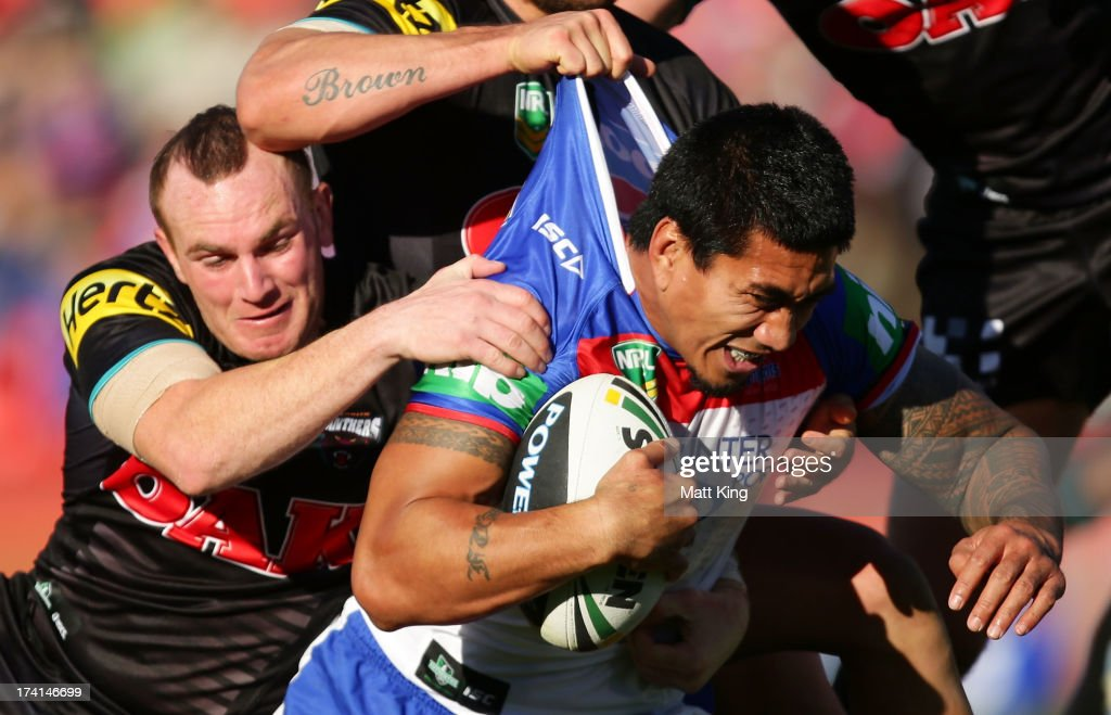 David Fa'alago of the Knights is tackled by Luke Walsh of the Panthers during the round 19 NRL match between the Penrtih Panthers and the Newcastle Knights at Centrebet Stadium on July 21, 2013 in Penrith, Australia.