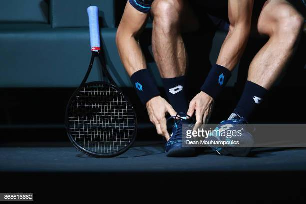 David Ferrer of Spain adjusts his shoe laces prior to his match against Adrian Mannarino of France during Day 2 of the Rolex Paris Masters held at...