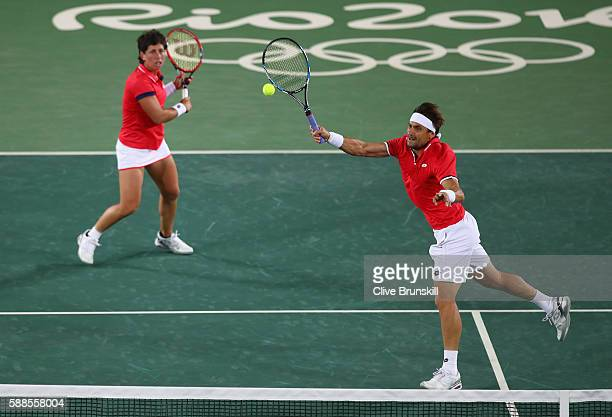David Ferrer of Spain and Carla Suarez Navarro of Spain in action during the mixed doubles first round match against Andy Murray of Great Britain and...