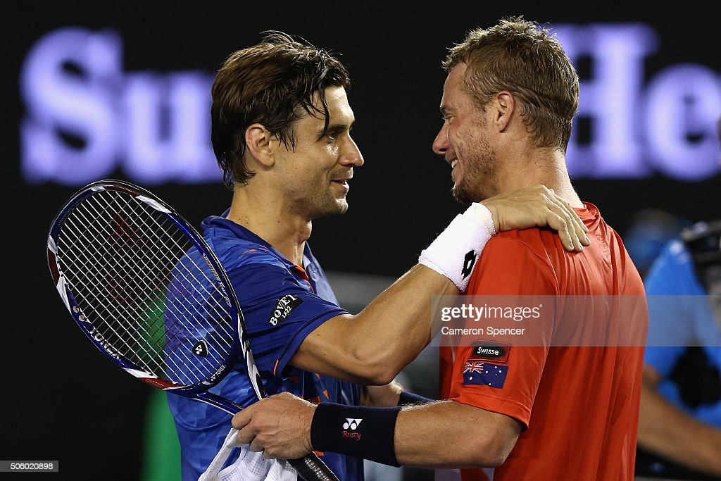 David Ferrer of Spain and Lleyton Hewitt of Australia meet at the net following their second round match and Hewitt's final match during day four of...