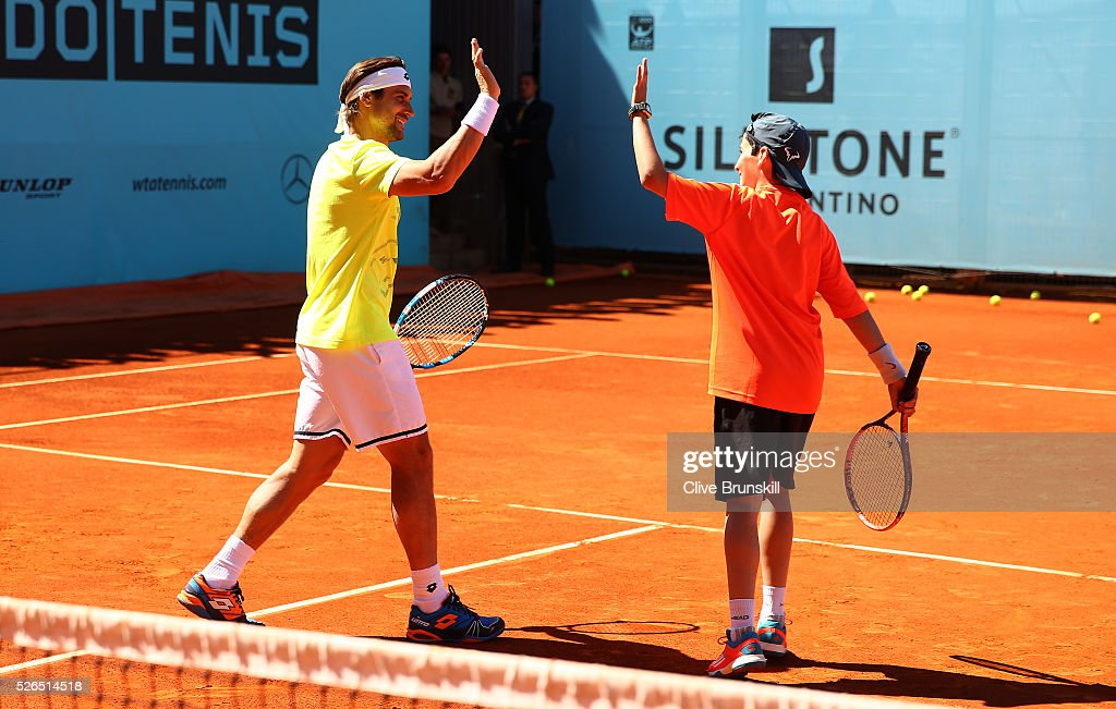 David Ferrer of Spain celebrates with a young player at a childrens tennis clinic during day one of the Mutua Madrid Open tennis tournament at the Caja Magica on April 30, 2016 in Madrid, Spain. .