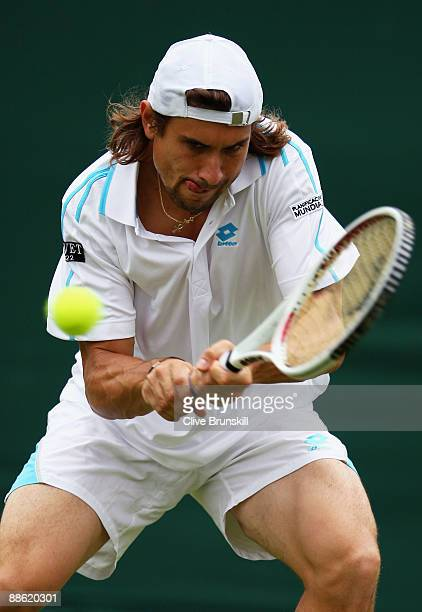 David Ferrer of Spain plays a backhand playing with Marc Lopez of Spain during the men's doubles first round match against Jeff Coetzee of South...