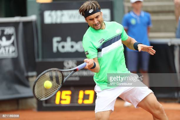 David Ferrer of Spain returns a ball to Alexandr Dolgopolov of Ukraine during the singles final match of the Swedish Open ATP tennis tournament in...