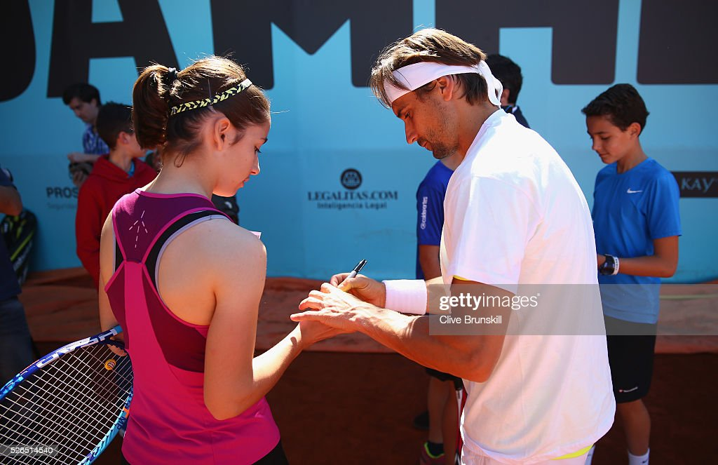 David Ferrer of Spain signs autographs after a childrens tennis clinic during day one of the Mutua Madrid Open tennis tournament at the Caja Magica on April 30, 2016 in Madrid, Spain. .