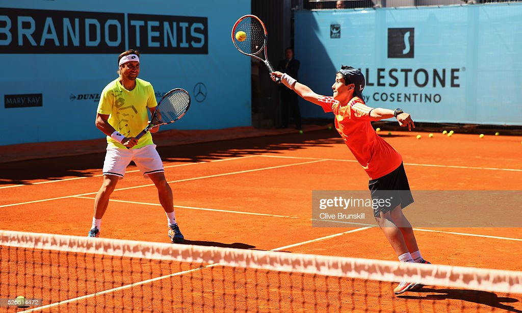 David Ferrer of Spain watches a young player at a childrens tennis clinic during day one of the Mutua Madrid Open tennis tournament at the Caja Magica on April 30, 2016 in Madrid, Spain. .