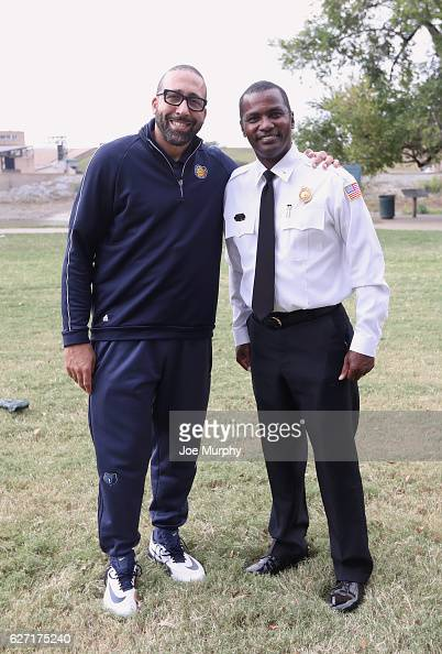 David Fizdale of the Memphis Grizzlies poses for a photo with a police officer during a visit to a prep school and then participates in an NBA Kids...