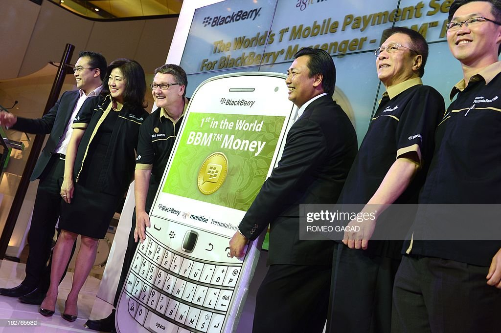 David Fletcher, (3L) President Director of Bank Permata and Maspiyono Handoyo (4L) Managing Director of Blackberry Inodnesia hold a mock Blackberry mobile phone during a ceremony in Jakarta on February 26, 2013 as the two companies launched the world's first instant messaging banking service in Indonesia, capitalising on the nation's addiction to the smart phone that is losing popularity in other key markets. The Blackberry service features 'BBM Money' that allows account holders with Bank Permata -- partly owned by Standard Chartered Bank -- to make peer-to-peer money transfers and top up their phone credit by sending funds to service providers. AFP PHOTO / ROMEO GACAD