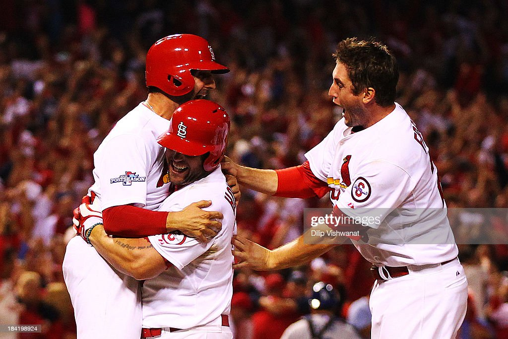 David Freese #23 and Daniel Descalso #33 and Matt Holliday #7 of the St. Louis Cardinals celebrate their to 2 win over the Los Angeles Dodgers in Game One of the National League Championship Series at Busch Stadium on October 11, 2013 in St Louis, Missouri.