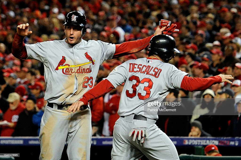 <a gi-track='captionPersonalityLinkClicked' href=/galleries/search?phrase=David+Freese+-+Baseball+Player&family=editorial&specificpeople=4948315 ng-click='$event.stopPropagation()'>David Freese</a> #23 and <a gi-track='captionPersonalityLinkClicked' href=/galleries/search?phrase=Daniel+Descalso&family=editorial&specificpeople=6800752 ng-click='$event.stopPropagation()'>Daniel Descalso</a> #33 of the St. Louis Cardinals celebrate after both score on a single by Pete Kozma #38 in the ninth inning against the Washington Nationals in Game Five of the National League Division Series at Nationals Park on October 12, 2012 in Washington, DC.