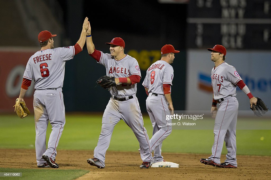 David Freese of the Los Angeles Angels of Anaheim celebrates with Mike Trout John McDonald and Collin Cowgill after the game against the Oakland...