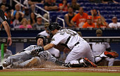 David Freese of the Pittsburgh Pirates scores as JT Realmuto of the Miami Marlins applies the tag during a game at Marlins Park on May 30 2016 in...