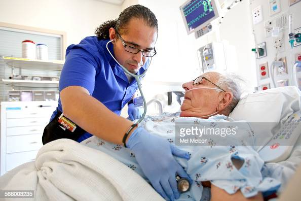 David Fuentes a student in the masters entry clinical nurse program at UCLA examines Russell Sherman a patient being treated for a pulmonary embolism...