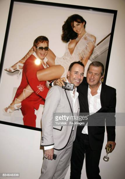 David Furnish and Mario Testino in front of an image of Elton John and Liz Hurley whilst attending the launch of Mario Testino's 'Obsessed By You'...