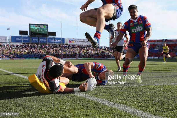 David Fusitu'a of the Warriors scores a try with Trent Hodkinson of the Knights in defence during the round 22 NRL match between the Newcastle...