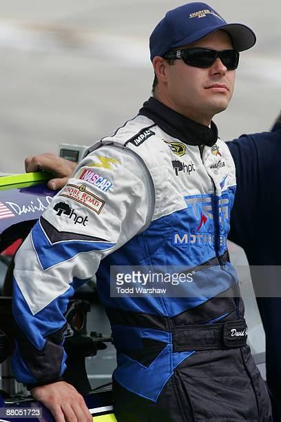 David Gilliland driver of the TRG Motorsports Chevrolet waits by his car during qualifying for the NASCAR Sprint Cup Series Autism Speaks 400 at...