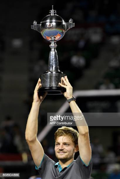 David Goffin of Belgium holds the trophy during the awarding ceremony after their men's singles final match against Adrian Mannarino of France during...