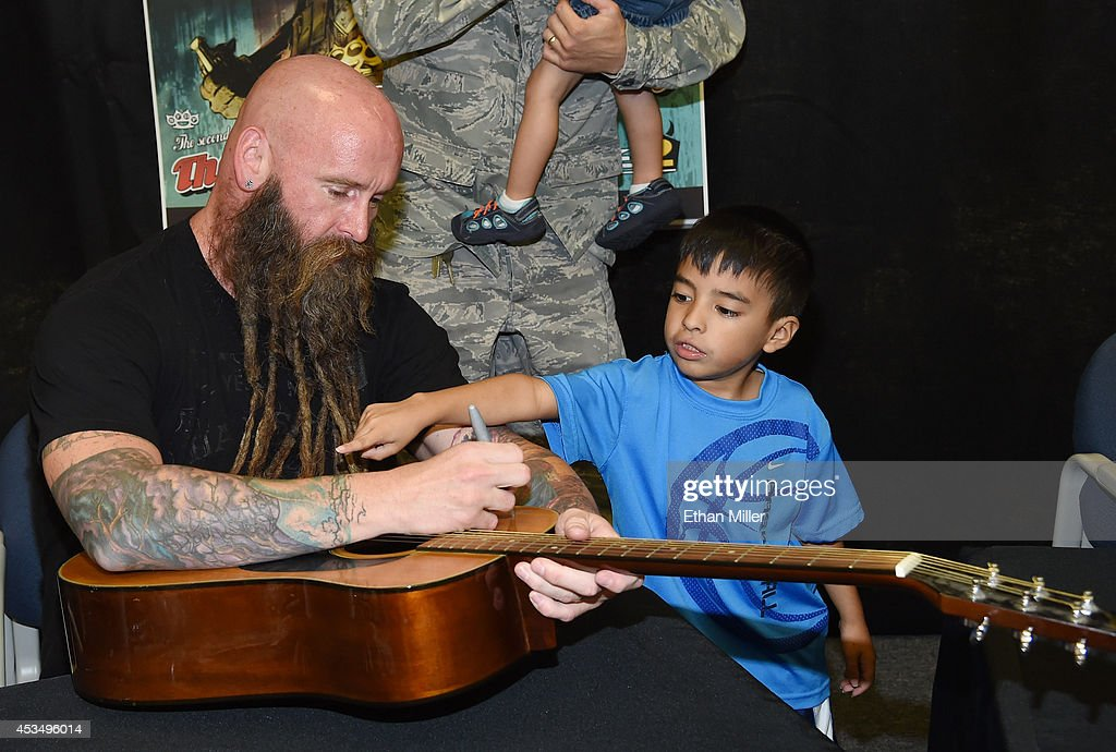 David Gregorich, 6, points at bassist Chris Kael of Five Finger Death Punch while he signs a guitar at Nellis Air Force Base as the band highlights its campaign to raise awareness about veterans suffering from post-traumatic stress disorder (PTSD), in part by launching the video 'Wrong Side of Heaven,' that deals with the subject on August 11, 2014 in Las Vegas, Nevada.