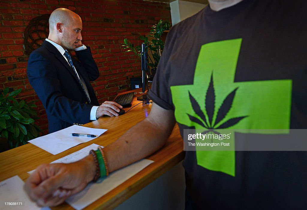 David Guard ( L ) verifies the identity of a man ( R ) before allowing him to purchase medical marijuana, the first legal sale, at Capital City Care in Washington, DC on July 29, 2013. Guard is the general manager of the business located at 1334 N. Capitol Street NW, in the DIstrict. Monday was their official opening day for legal sale of medical marijuana in the nation's capital. Buyers must have a district issued-photo ID to purchase different grades of the substance. The store also sells paraphenalia for ingesting the substance.