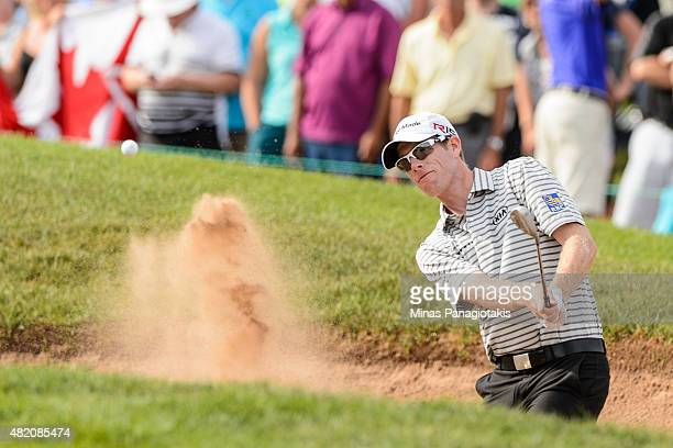 David Hearn of Canada shoots from the bunker on the eighteenth hole during the final round of the 2015 RBC Canadian Open at Glen Abbey Golf Course on...