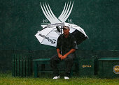 David Hearn's caddie Brent Everson waits under an umbrella on the first tee during the weatherdelayed second round of the 96th PGA Championship at...